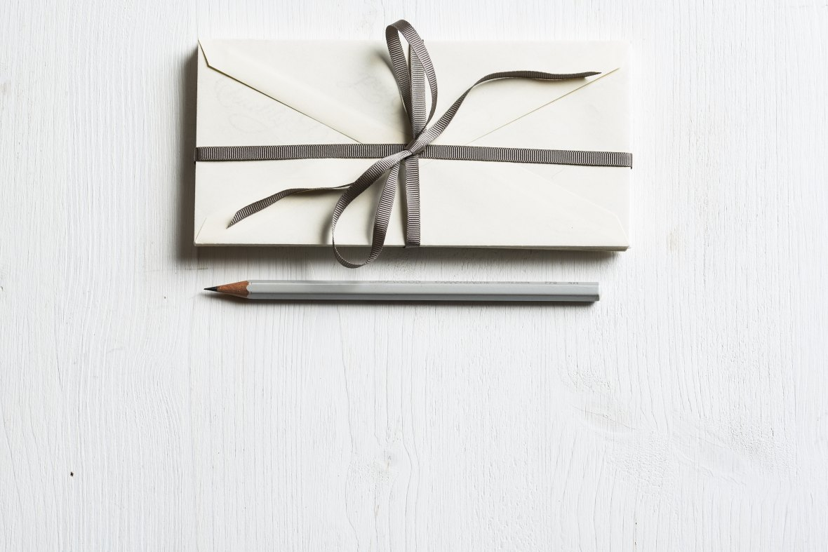 Enveopes tied with a neat bow and a sharpened pencil.