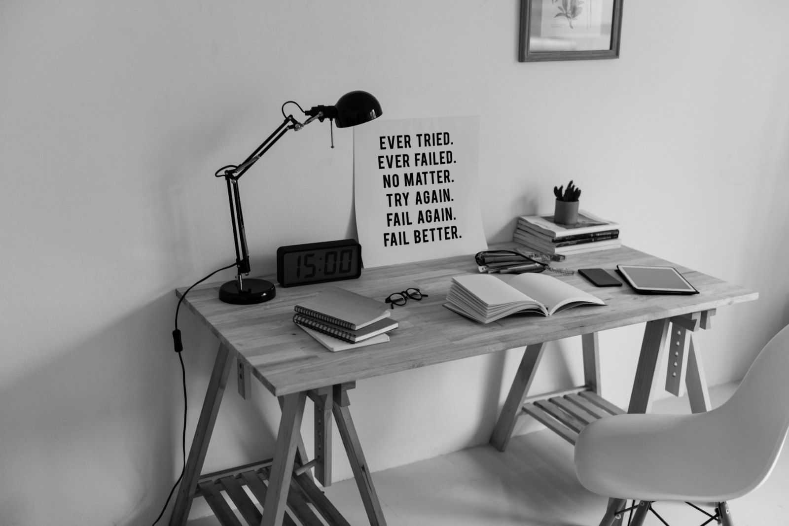 Small home office desk with a determind quote board.